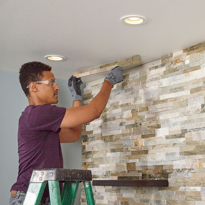 Cutting and placing the top line of stone on the wall | Construction Pro Tips