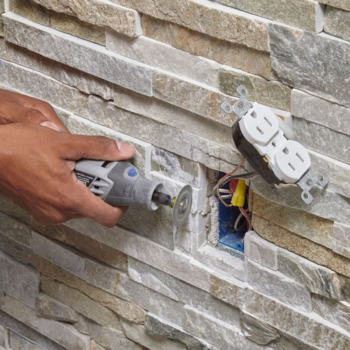 Grinding out the stones around the outlet space | Construction Pro Tips