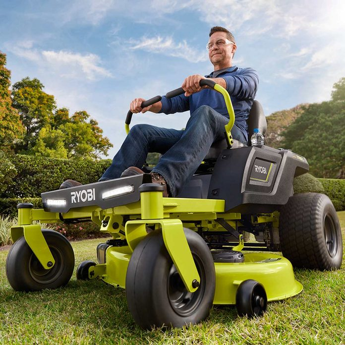 Man on a Ryobi Battery Powered Zero Turn Riding Lawn Mower