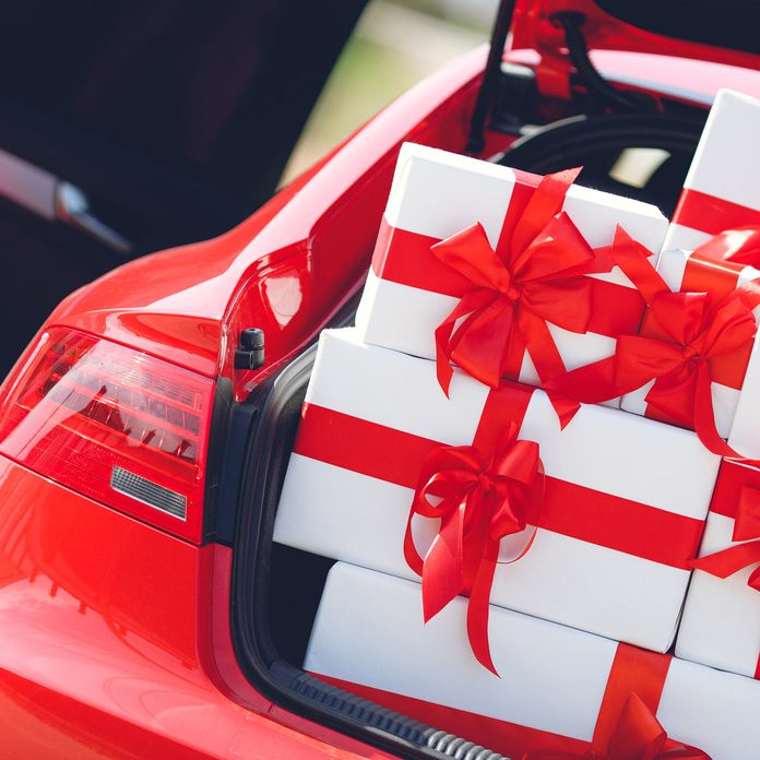 red luxury car with trunk full of gift boxes. presents for holiday. car, presents. holidays, happiness. street outdoor