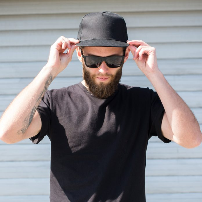Hipster man wearing black T-shirt and a black hat with space for logo
