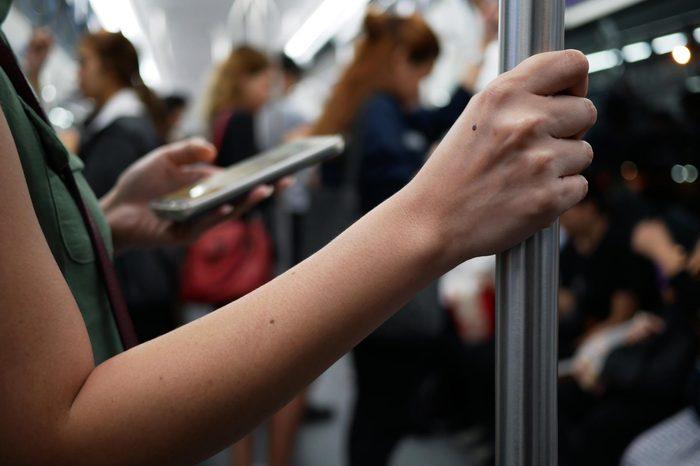 closeup woman hand holding handrail inside the train.