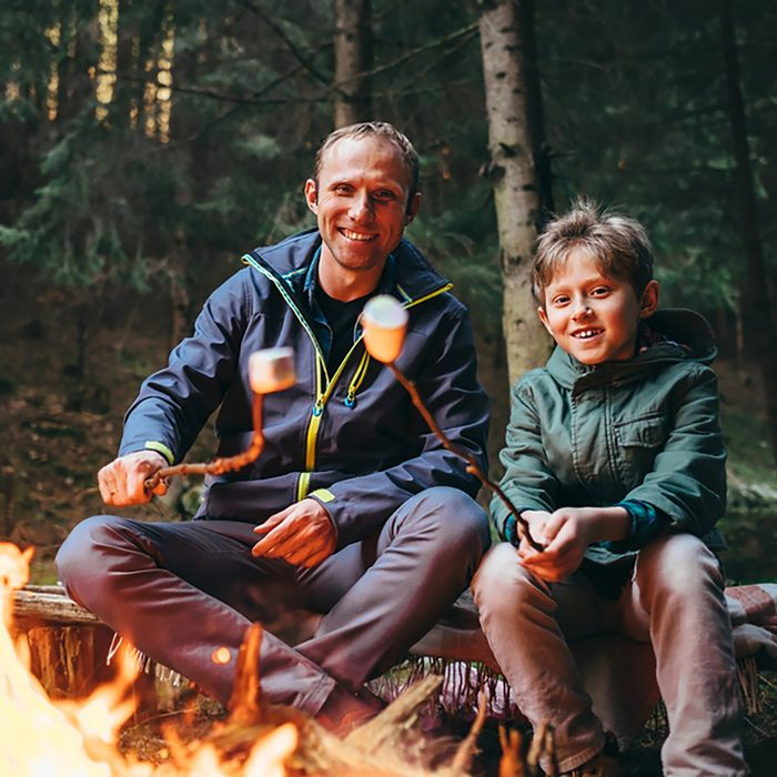 Father & son agree meal planning for group camping makes trips so much better as they roast marshmallows over the campfire