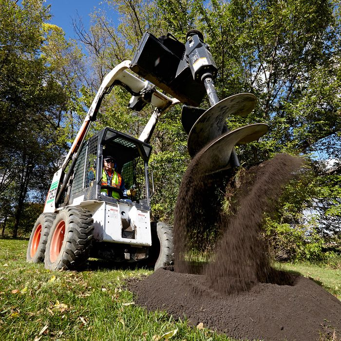 pro landscaper digging up dirt with an auger