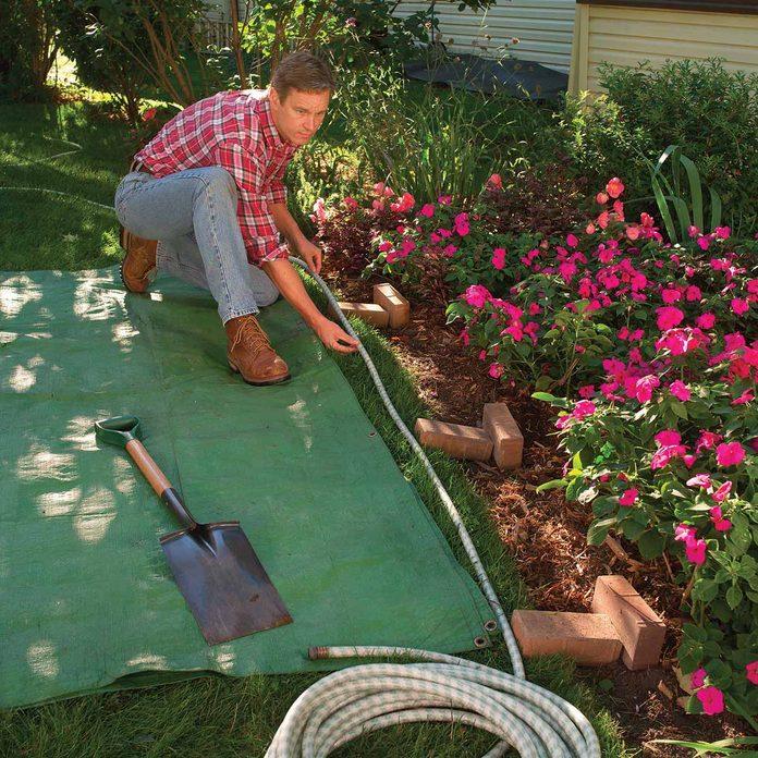 Man measures garden bed edge with a garden hose