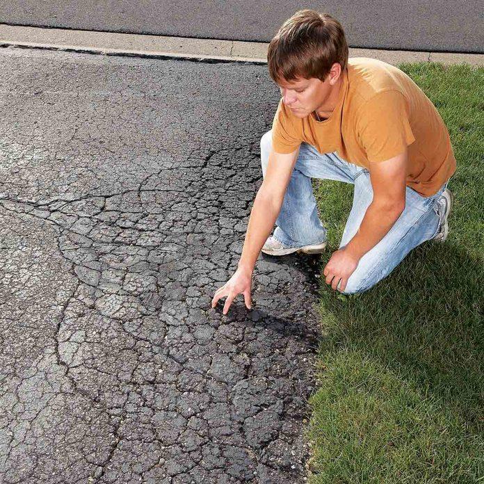 Man-examines-a-cracked-and-crumbling-asphalt-driveway