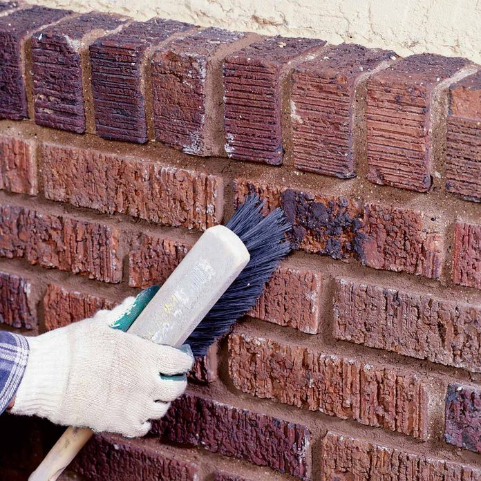 Woman brushes bricks clean after adding motar to joints