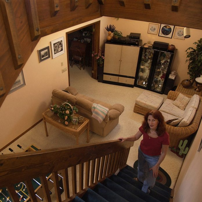 Woman stands in a the stairwell of an underground home