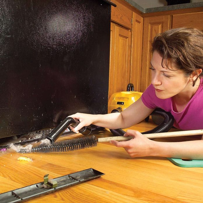Woman-cleans-dirty-refrigerator-coils-with-vacuum