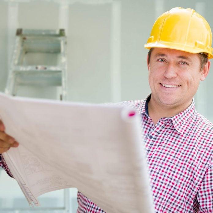 Man wearing a hard hat looks at blueprints