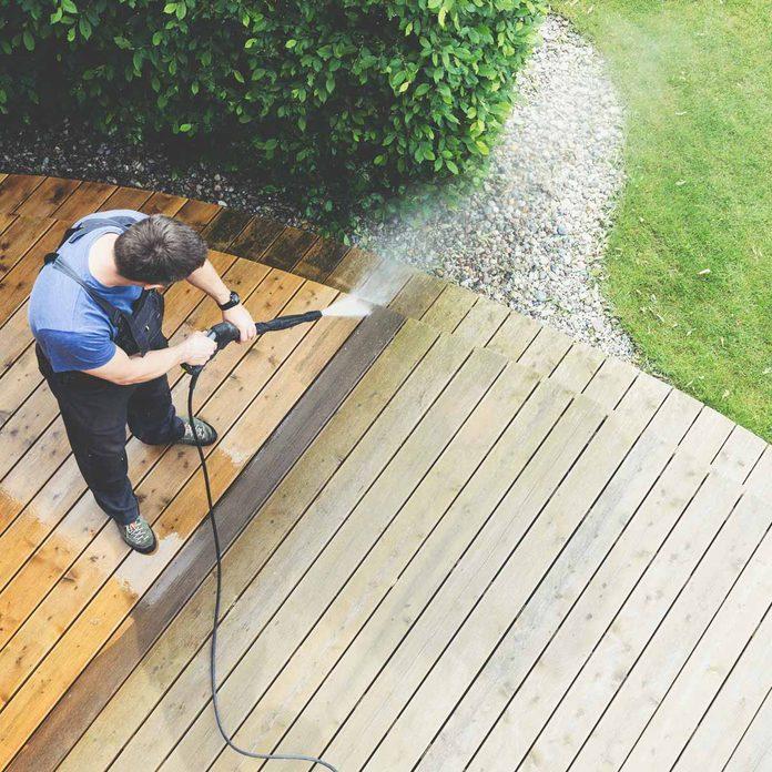Man-pressure-washes-a-deck