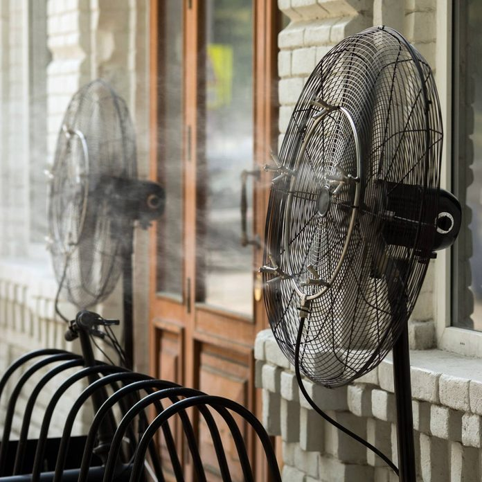 Contemporary system of fans with pulverizes spraying water with air and cooling air outdoors in hot summertime