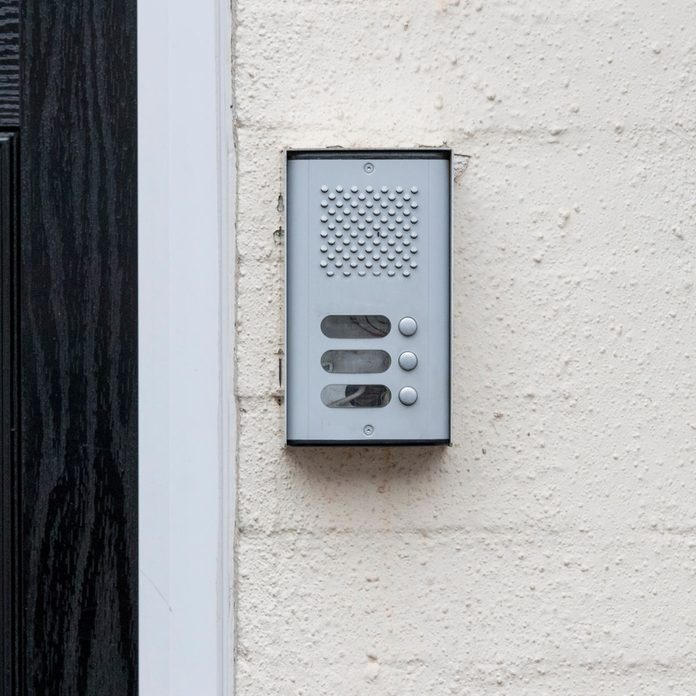 residential-buzzer-intercom-next-to-a-black-door-on-a-white-wall