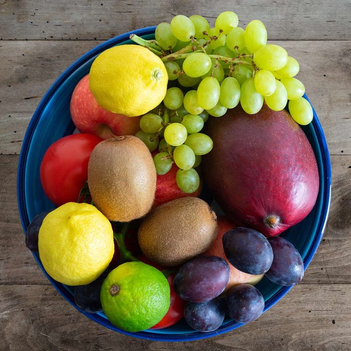 top-view-of-bowl-filled-with-fresh-fruits-on-rustic-wooden-table