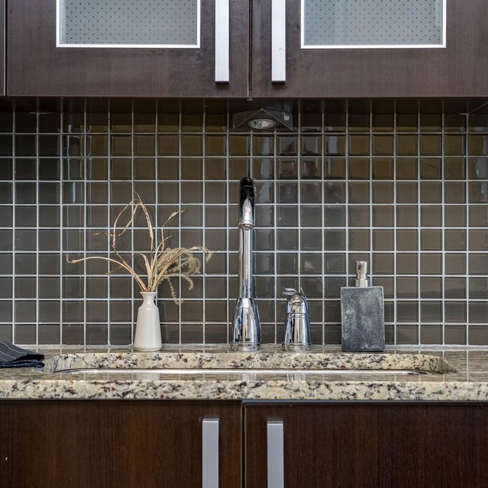 Black-tile-backsplash-in-a-kitchen-with-dark-cabinets