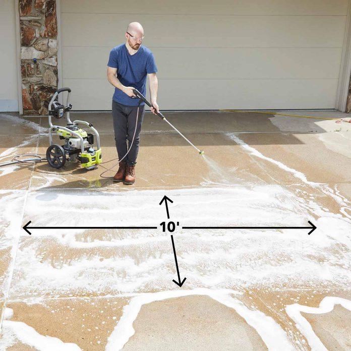 Spraying soap on concrete driveway
