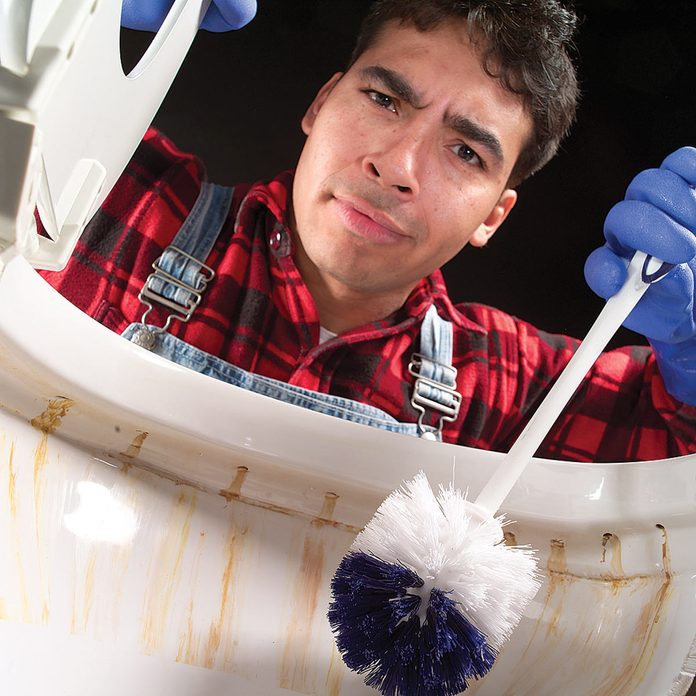 Man holds toilet brush above toilet with rust stains.