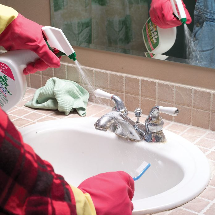 Man sprays a cleaning product on a bathroom faucet while holding a toothbrush