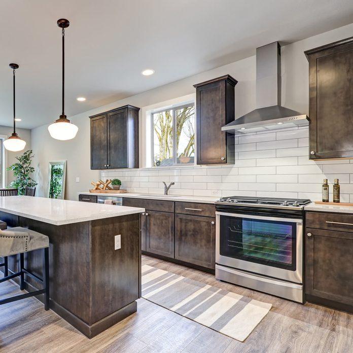 New-kitchen-boasts-dark-wood-cabinets-white-backsplash-subway-tile-and-over-sized-island-with-white-and-grey-quartz-counter-illuminated-by-pendant-lights