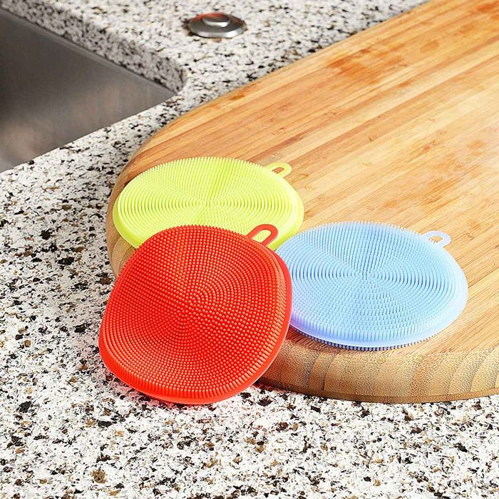collection of silicone sponges on a wooden cutting board