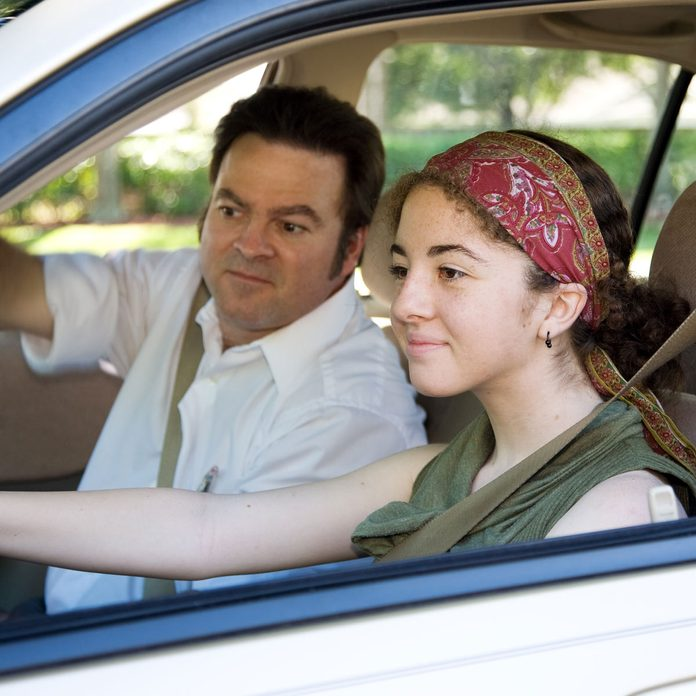 Teenage-girl-checks-her-driver-side-mirror-while-father-watches-in-car