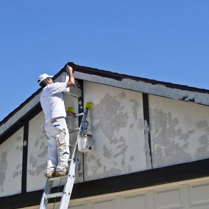 Painter on a ladder uses brown paint