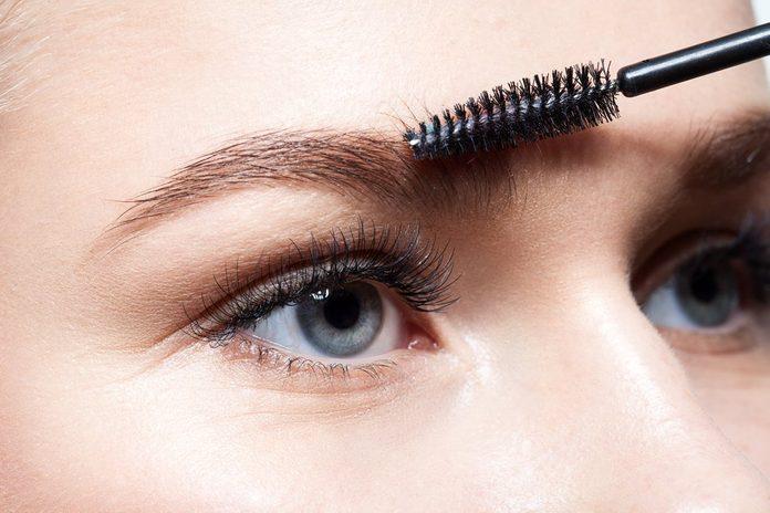 Closeup of a young woman doing makeup eyebrow brush