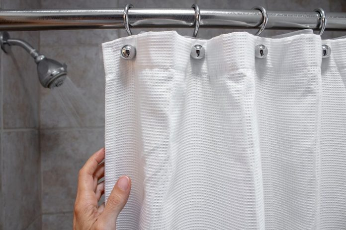 a hand pulling back a shower curtain revealing a shower head with water on horizontal shot