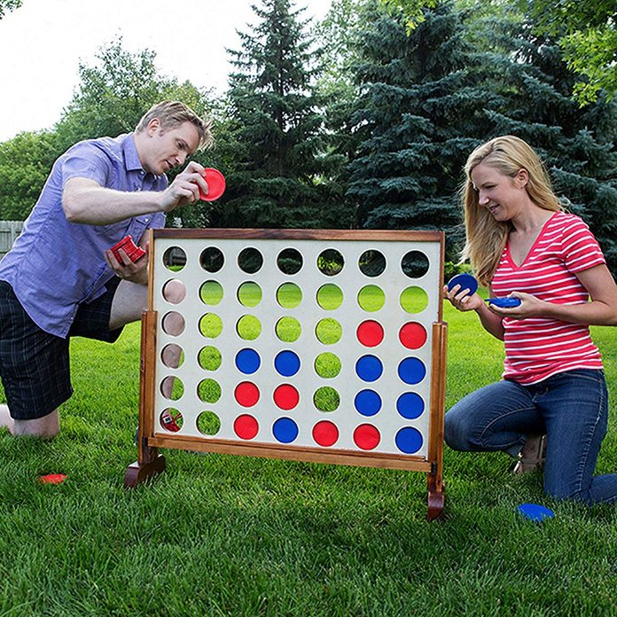 Two people playing connect four in the lawn