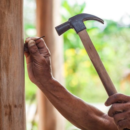 The carpenter is repairing the house. He makes nails using a hammer