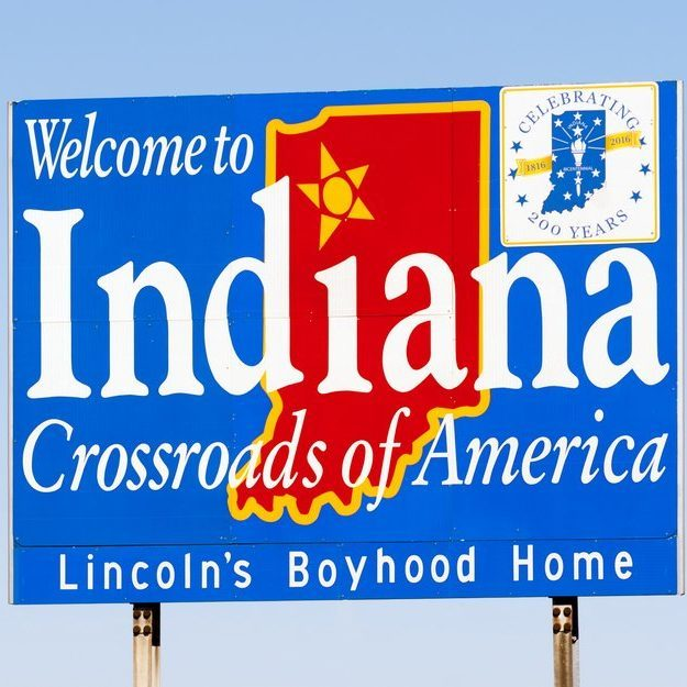 Blue sign against blue sky welcomes you to Indiana
