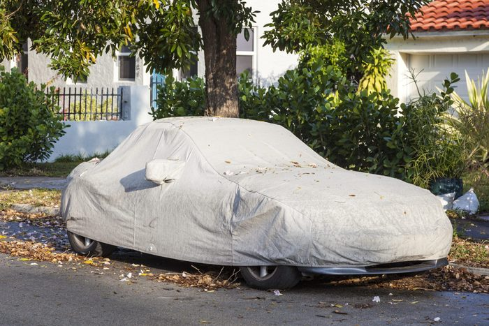 Car under a protective cover parked on the roadside in the city