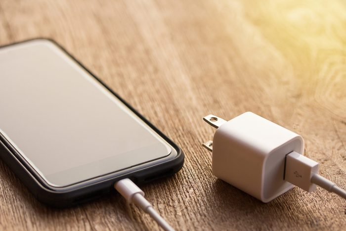 Close up of black smartphone charging battery with cable on wooden table and sunlight with copy space and blurry background. Vintage tone and soft light. Selective focus.
