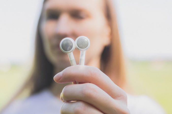 Young woman holds in her hands white earbud headphones