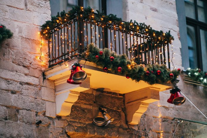 Stylish christmas decorations, red jingle bells, lights, fir branches with ornaments on balcony in european city street. Festive decor and illumination in city center, winter holidays
