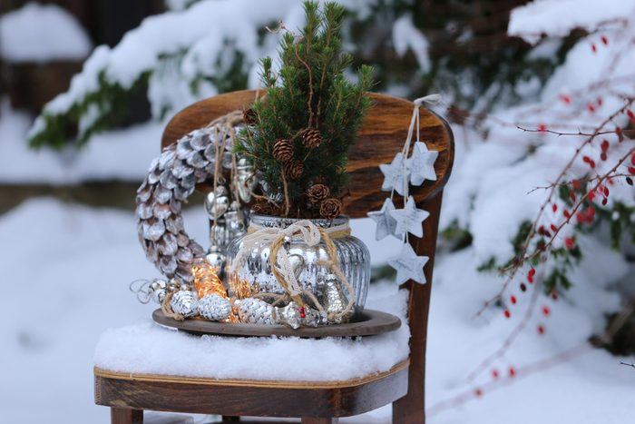 Winter composition with Christmas wreath, glass decoration, garland, fir tree, wooden star on vintage wooden child chair on snow, natural background, outdoor and space, scene in snow garden