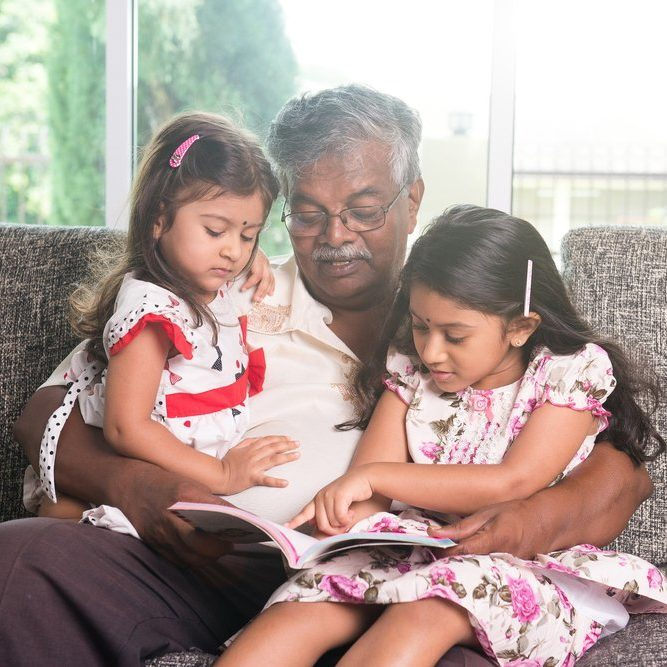 indian grandfather learning with his granddaughters