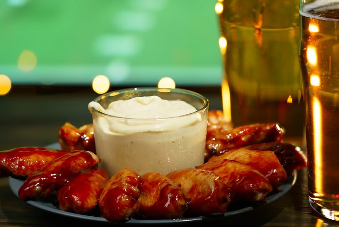 Hot barbecue chicken wings with 2 beer glasses on a dark wooden table served with honey mustard sauce. Football on a background