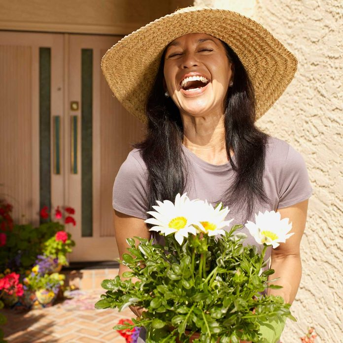 Woman planting flowers to increase curb appeal