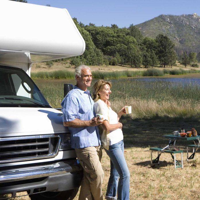 Couple drinking coffee against their RV