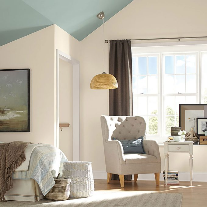 Bedroom with white walls and a blue ceiling