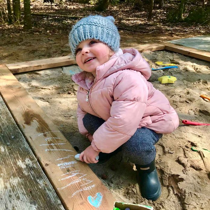 Little girl playing in a sand box