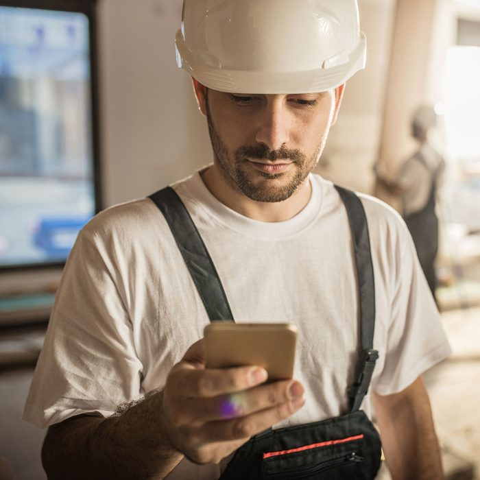 Construction worker adjusting tool setting on a smart phone
