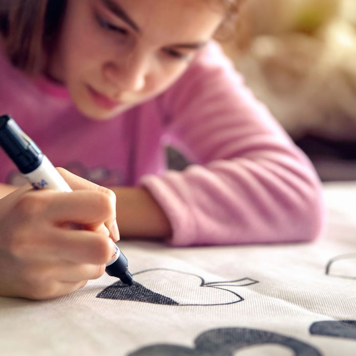 Girl drawing on fabric