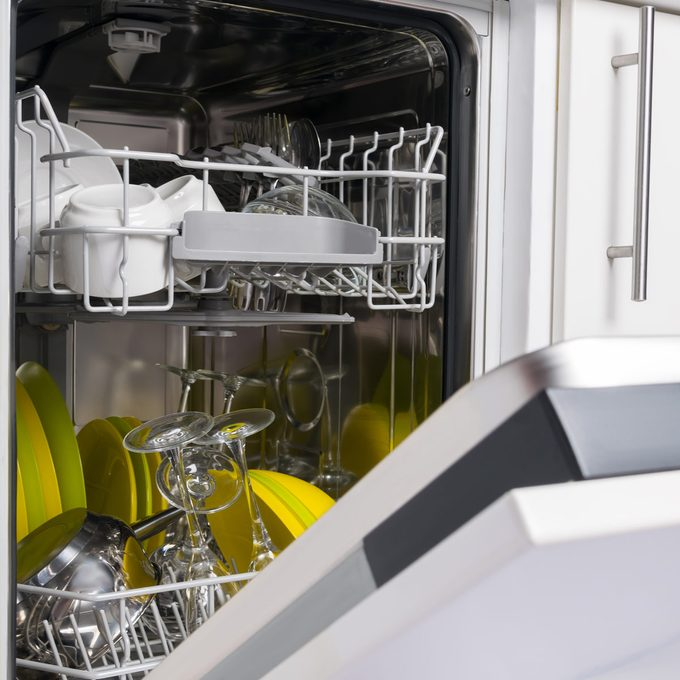 open dishwasher door with clean dishes inside