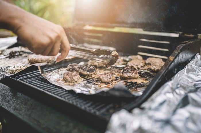 close up on the barbecue grill with a tong turning the meat during cooking