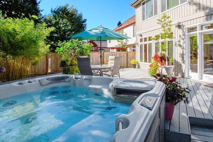 view of a hot tub in the foreground with a deck, outdoor table and chairs, and a house in the background