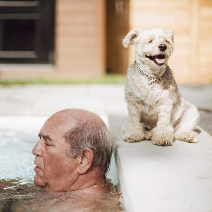 senior man sitting in hot tub while his dog sits besides him