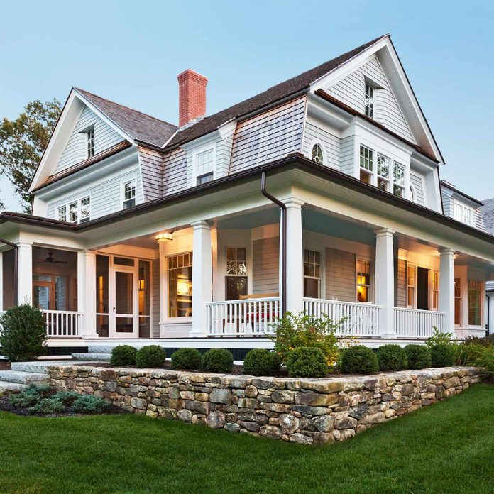 Exterior view of custom built home with exterior lighting and manicured landscaping home architecture