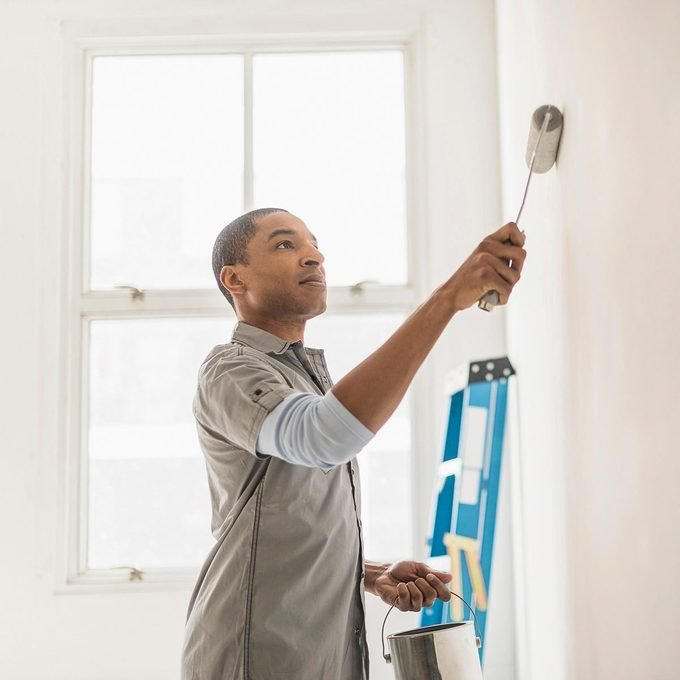 Black man painting wall of home